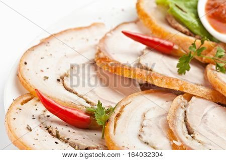 Freshly sliced cold meat decorated with red chili pepper