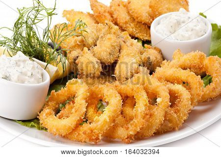 Plate of fried in batter squid and mussels with sauce