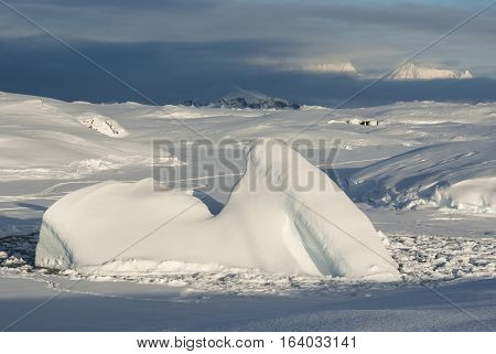 small iceberg frozen into the Straits on the background of the old station in Antarctica and mountains