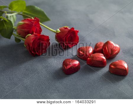 Bouquet of red roses and hart shaped chocolates. A valentines day concept