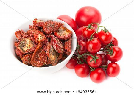 Sun dried tomatoes in white bowl and heap of ripe fresh tomatoes isolated on white background