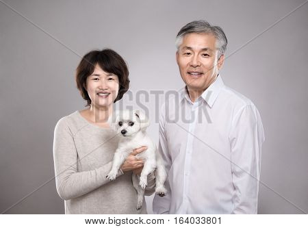 Happy Asian middle-aged couple with puppy studio portrait - isolated
