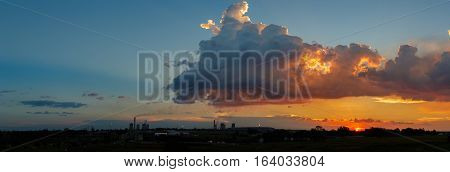 Vibrant color cumulonimbus clouds sunset orange Industrial skyline of constantly smoking chimneys from coal burning chemical engineering petroleum plant. Flames consume expelled toxic gas.