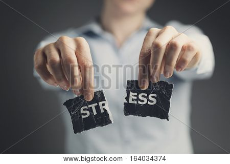 Woman holding a torn label with the word stress toward the camera.