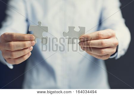 Businesswoman holding two matching jigsaw puzzle pieces next to each other. Shallow focus.