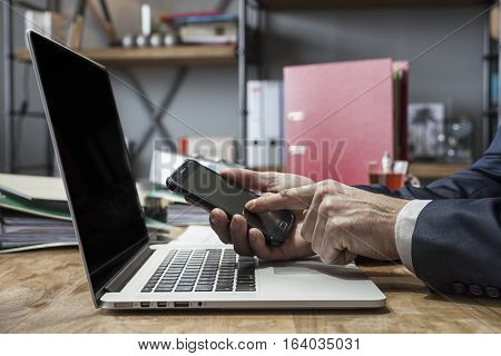 Portrait of businessman sitting at home and using his laptop while working on new project.