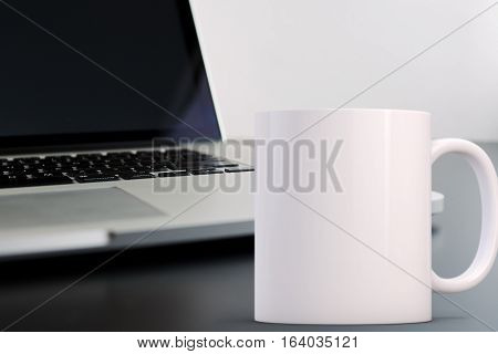 Mockup Styled Stock Product Image white mug that you can add your custom design/quote to. Mug is in front of an open laptop.