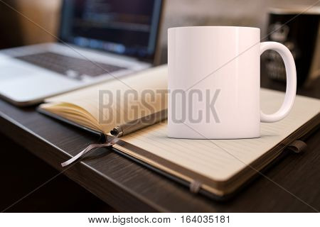 Mockup Styled Stock Product Image white mug that you can add your custom design/quote to. Mug is on an open notebook next to a laptop.