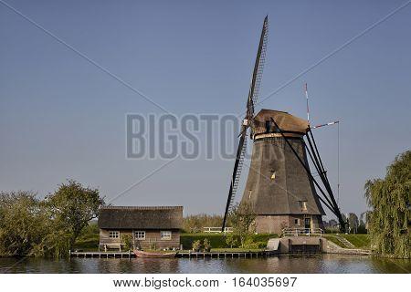 Dutch windmill at Kinderdijk an UNESCO world heritage site. Stone brick Windmill with water.