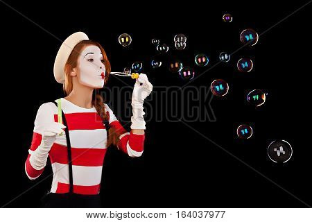Portrait of the female MIM comedian blows soap balls isolated on black background.