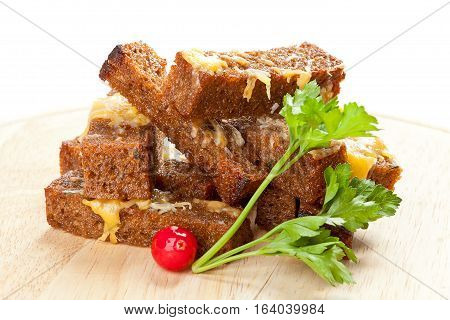 Snack roast rusk from dark bread with cheese on wooden board.White background