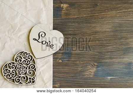 Wooden valentine hearts on natural wooden background concept of eco romance and love