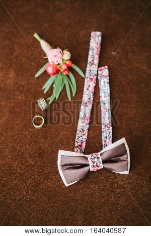 groom's accessories for a wedding. bow tie, buttonhole and rings close up. preparation for a wedding. set groom.