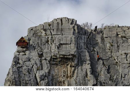 Red wooden climber house in the Lakatnik rocks and Alpine climber, Iskar river defile, Sofia province, Bulgaria