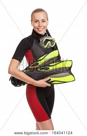 Young smiling blond woman in a wet suit for swimming poses holding flippers. Studio short. Isolated on white background.