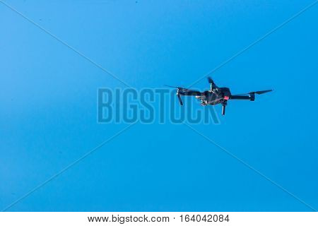 Small grey modern drone hovering against blue sky