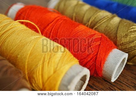 Row of colorful spools with yellow, brown, green, red and blue threads used for sewing as a symbol of housework, needlework and handwork
