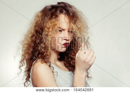 people youth and beauty concept - Beauty woman with curly big and long hair. Permed hair. Glamour lady Beauty Girl grey background. Beautiful Woman Portrait. Blond Wavy Hair. unhappy girl hair