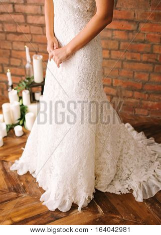 the beautiful bride in a white guipure elegant dress. the bride against the background of a brick wall and candles.