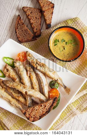 capelin fish fried in batter with sauce