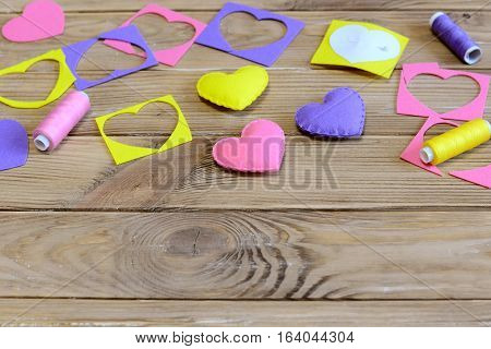 Valentine's day hearts DIY. Colorful hearts presents made of felt, felt scraps, paper template, thread on wooden table. Valentine's day handmade gifts project. Handicrafts background with copy space