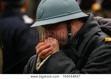 BUCHAREST ROMANIA - DECEMBER 1 2010: A soldier warms his hands during a military parade on National Day of Romania. More than 3000 soldiers and personnel from security agencies take part in the massive parades on National Day of Romania.