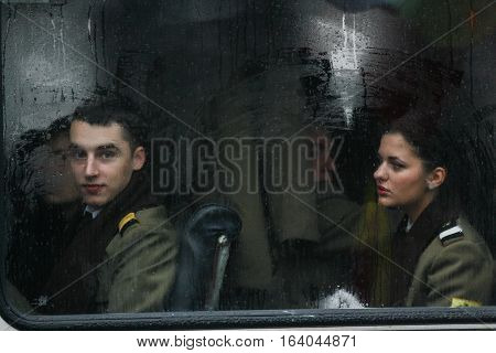 BUCHAREST ROMANIA - DECEMBER 1 2010: Military are seen behind a bus window during a military parade. More than 3000 soldiers and personnel from security agencies take part in the massive parades on National Day of Romania.
