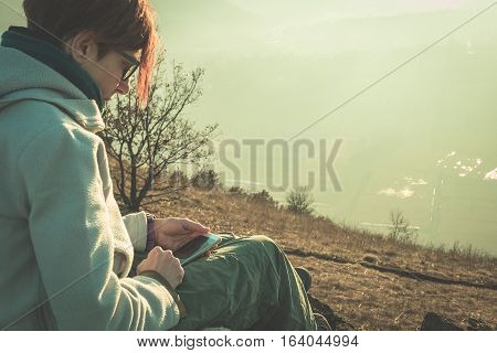 Woman using smart phone outdoors in the countryside. Rear side view in backlight toned image vintage style. Concept of people sharing informations with new technology while traveling.