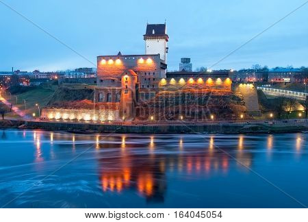 NARVA, ESTONIA - JANUARY 1, 2017: Hermann Castle Museum on the bank of The Narva (Narova) River. On the right side is The Bridge of Friendship between Estonia and Russia. View from Russian territory
