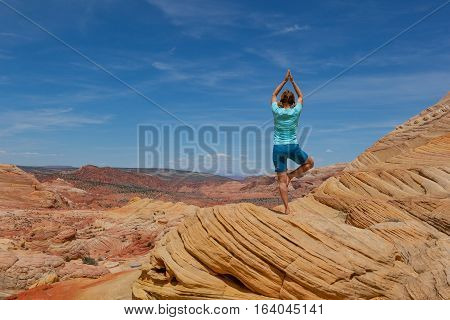 Yoga in the red rock desert of The Wave Coyote Buttes Paria Canyon-Vermilion Cliffs Wilderness, Utah, United States of America