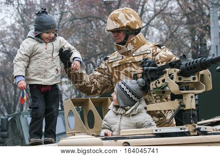 BUCHAREST ROMANIA - DECEMBER 1 2008: A soldier is paying with a child during a military parade on National Day of Romania. More than 3000 soldiers and personnel from security agencies take part in the massive parades on National Day of Romania.