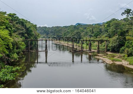 Crumbling iron and concrete walking bridge crossing large river in rain forest of Cameroon, Africa on an overcast day.