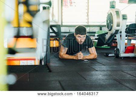 Young athlete doing exercise strap - Plank standing on his elbows at the gym. It notes the time on the phone looking toward the camera.