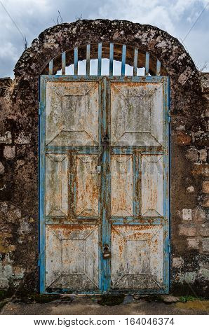 Old rusty door with pad locks and rock arch at historical palace of the Fon, Bafut, Cameroon, Africa.