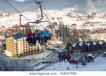 Skiers rising up on a chairlift with hotels and apartments on the background in Bukovel winter resort December 2016