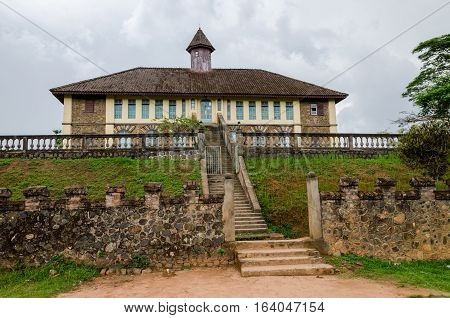 Museum at traditional palace of the Fon of Bafut with brick and tile buildings and jungle environment, Cameroon, Africa.