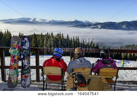 Young people with snowboards enjoying beautiful mountain landscape on a café terrace in Bukovel winter resort Ukraine December 2016.