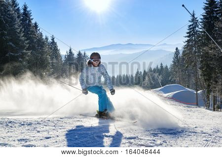 Happy young woman skiing on a winter resort with beautiful mountains on the background