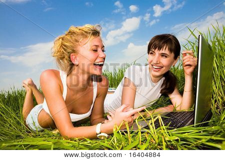 Two beautiful girl in white clothes on a laptop computer outdoors. Lay on the green grass.