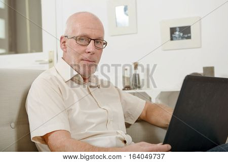 mature man using laptop on the sofa at home