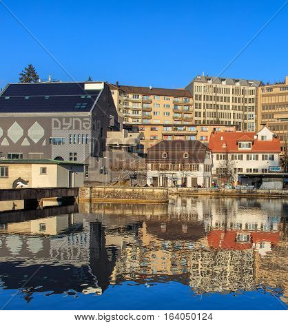 Zurich, Switzerland - 1 January, 2017: the Limmat river, buildings along it, people on the embankment. The Limmat is a river, which commences at the outfall of Lake Zurich in the southern part of the city of Zurich.