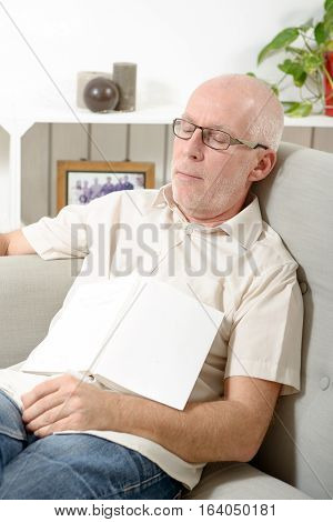 handsome mature man taking a nap in sofa at home