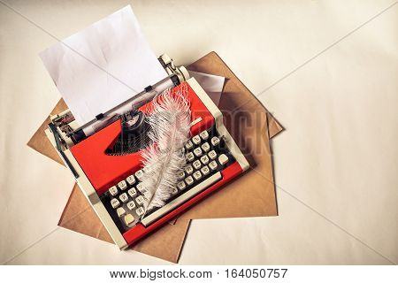 Red vintage typewriter with white blank paper sheet, blank envelopes and white ostrich feather on table. Toned image