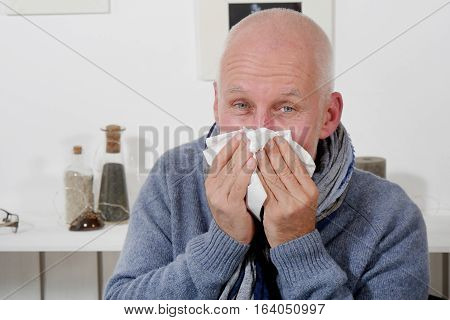 mature man who has flu is blowing his nose