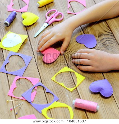 Child made hearts out of felt. Children's hands on the table. Handmade Valentines day heart gifts, crafts materials and tools on a wooden table. Valentine's day craft project