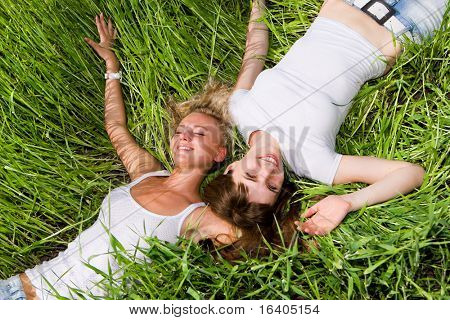 Two beautiful young women lay on the green grass outdoors.