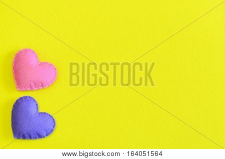 Two felt hearts isolated on yellow background with copy space for text. Valentine's day, wedding or mother's day background or card. Handmade felt hearts decorations. Top view