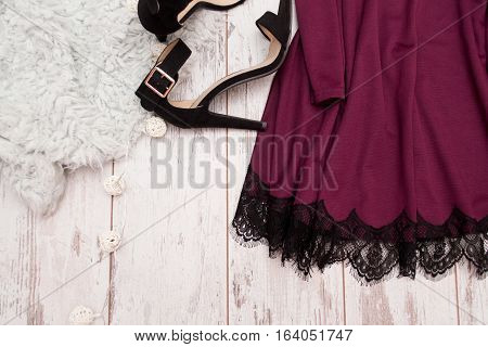 Part purple dress with lace and black shoes on a wooden background fashionable concept space for text