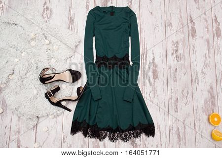 Emerald dress with lace black shoes and a Imitation fur on a wooden background fashionable concept top view