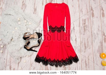 Red dress with lace black shoes and a Imitation fur on a wooden background fashionable concept top view